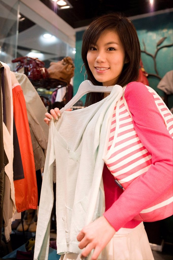 Young Woman Looking At Clothes In Shop : Stock Photo