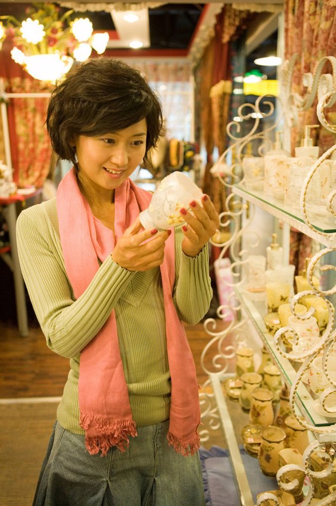Stock Photo: 1839R-5560 Young Woman Looking At Objects In Shop