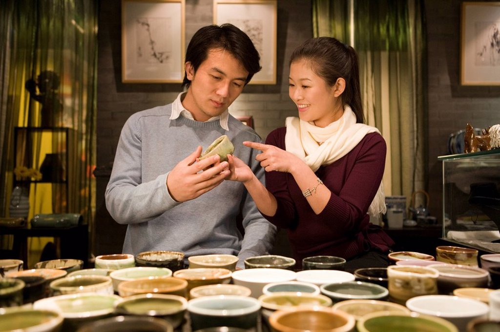 Stock Photo: 1839R-5569 Young Couple Looking At Objects In Shop
