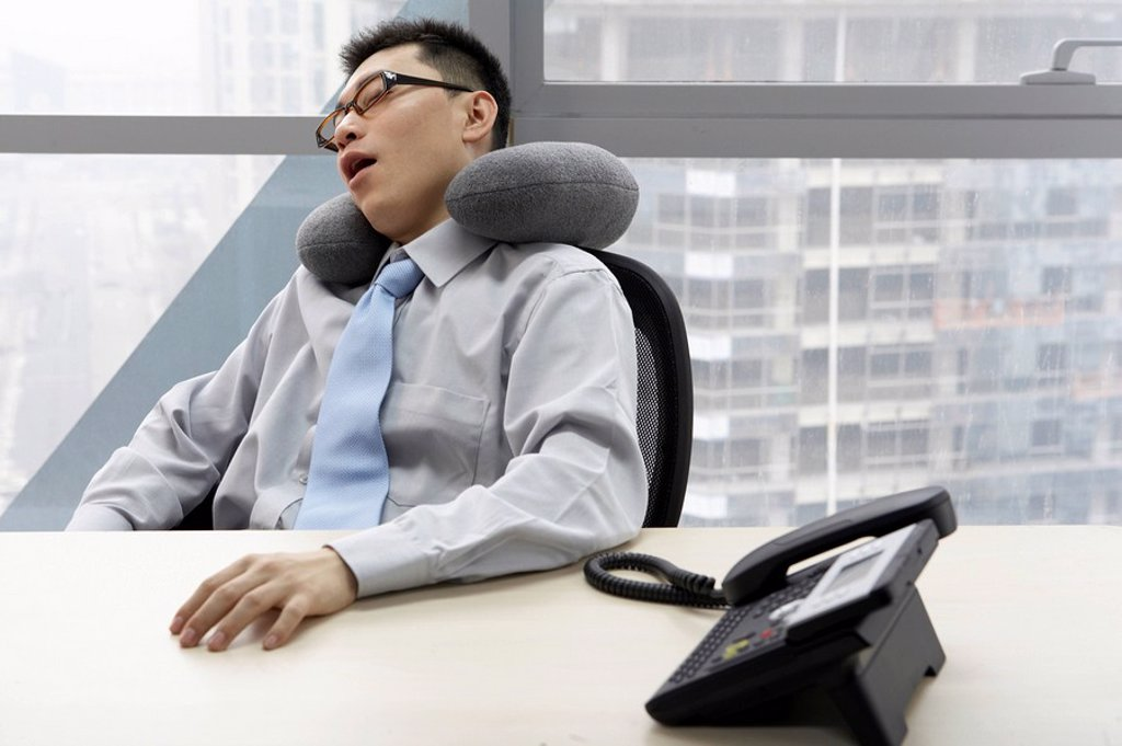 Stock Photo: 1839R-5741 Businessman In Office Resting With Neck Pillow