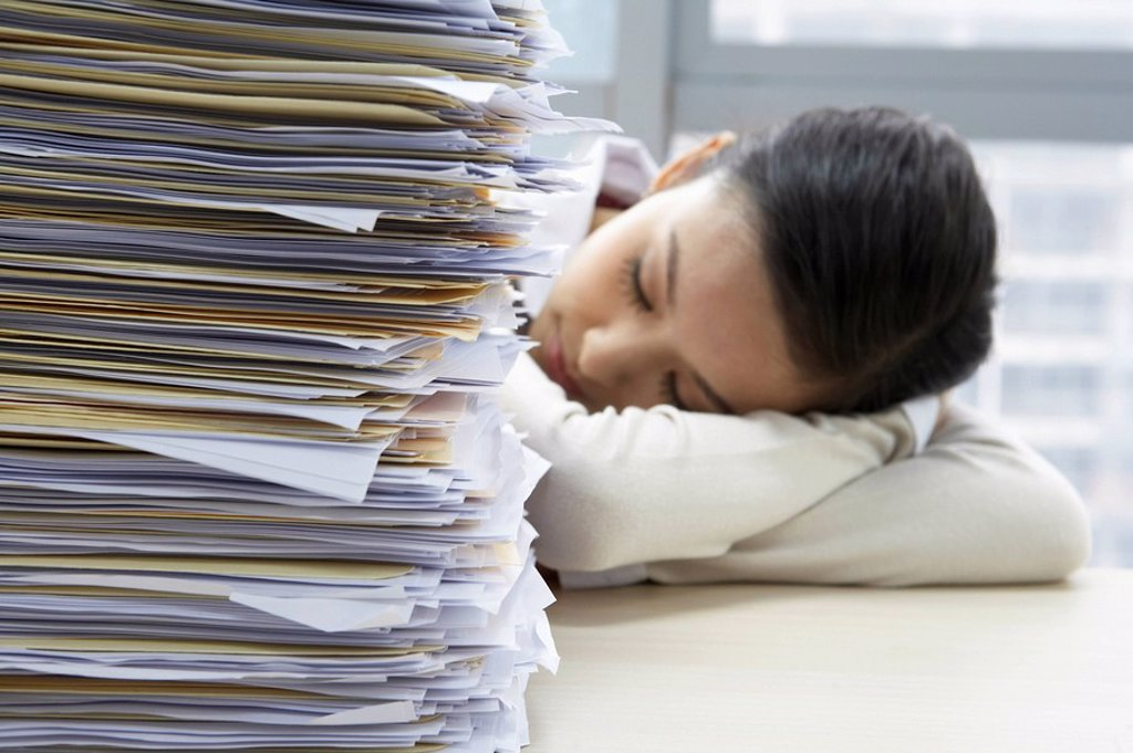 Businesswoman Sleeping Next To Pile Of Work : Stock Photo