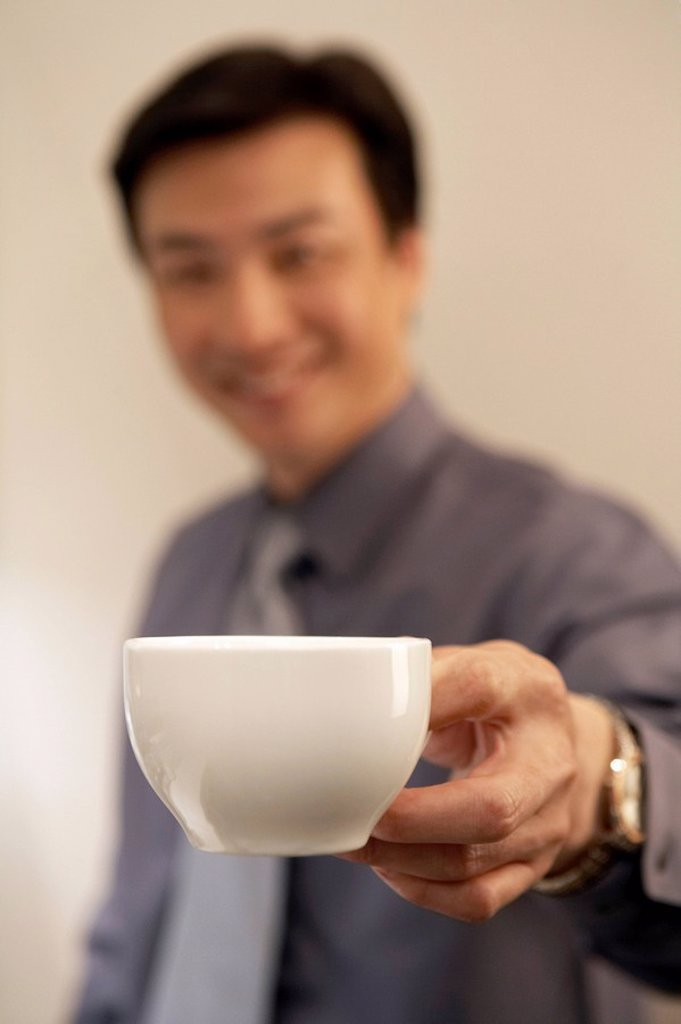 Stock Photo: 1839R-5812 Young Man Holding Coffee Cup
