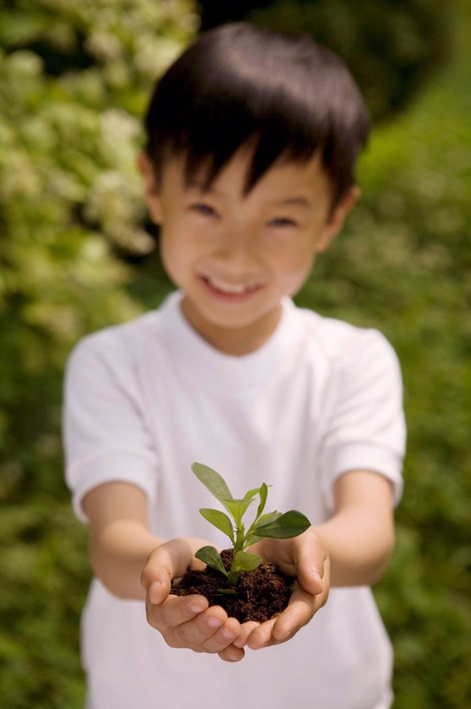 Stock Photo: 1839R-6229 Young Boy Holding Plant In Both Hands