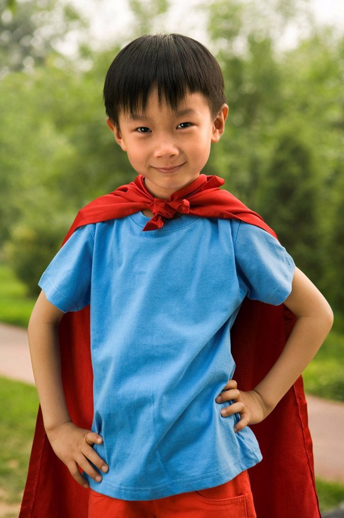 Boy In Red Cape Playing In Garden : Stock Photo