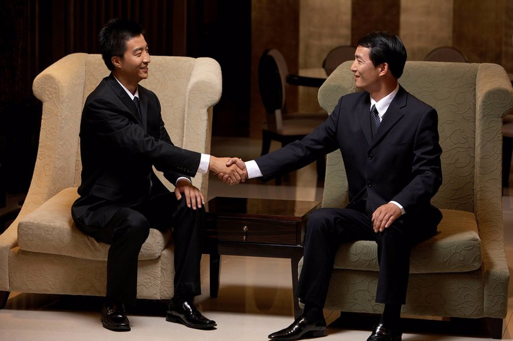 Two business leaders shake hands at an exclusive business club : Stock Photo