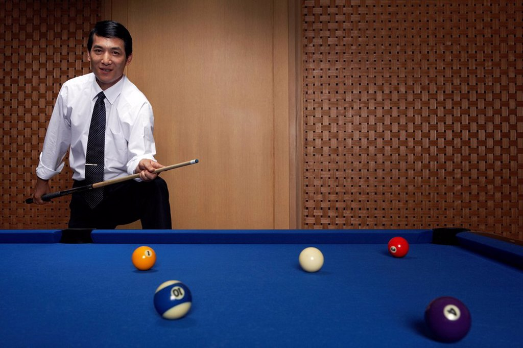 Stock Photo: 1839R-6826 Portrait of a businessman at the billiards table