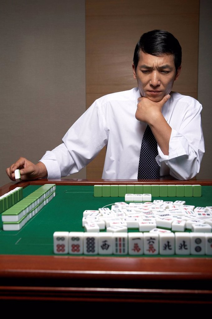 A businessman plays Mahjong : Stock Photo