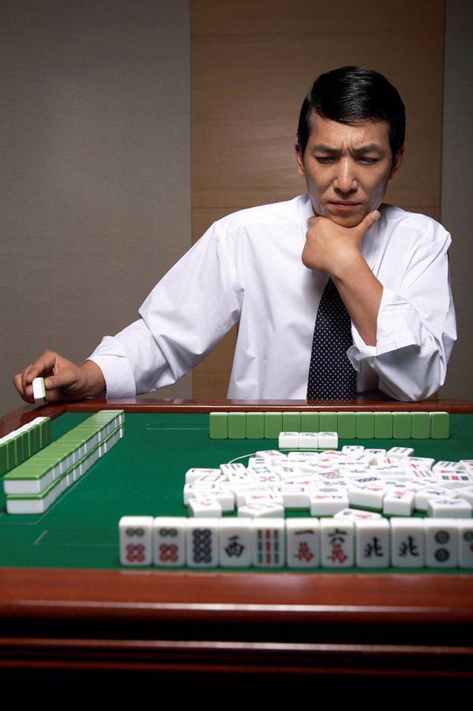 Stock Photo: 1839R-6835 A businessman plays Mahjong