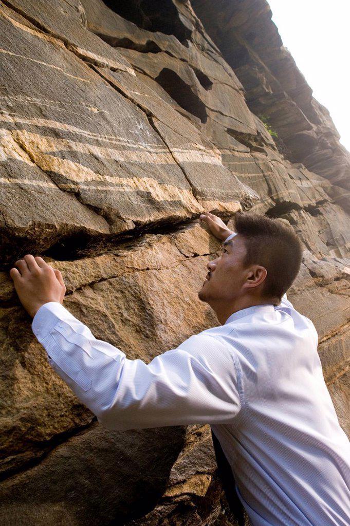 A businessman climbing a rock face : Stock Photo