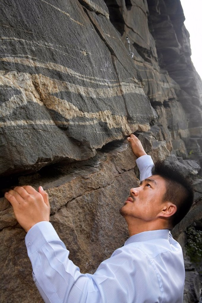 Stock Photo: 1839R-7117 A businessman climbing a rock face