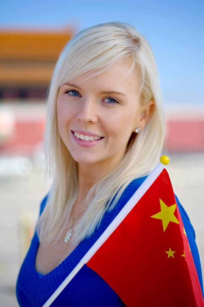 Young woman holding a flag in front of Tiananmen Gate, Beijing, China : Stock Photo