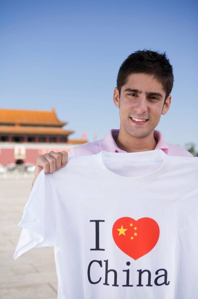 Young man holds an I Heart China t_shirt in front of Tiananmen Gate, Beijing, China : Stock Photo
