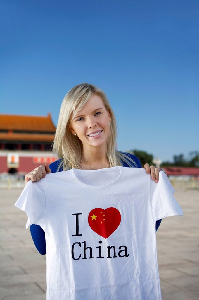 Young woman holds an I Heart China t_shirt in front of Tiananmen Gate, Beijing, China : Stock Photo