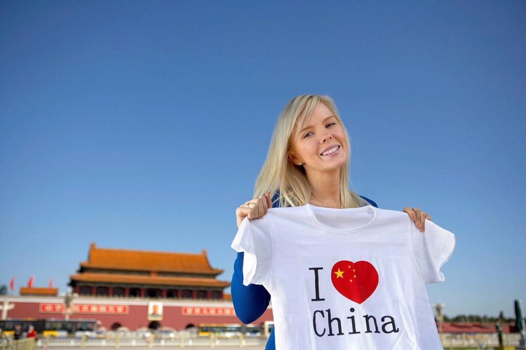 Stock Photo: 1839R-7447 Young woman holds an I Heart China t_shirt in front of Tiananmen Gate, Beijing, China