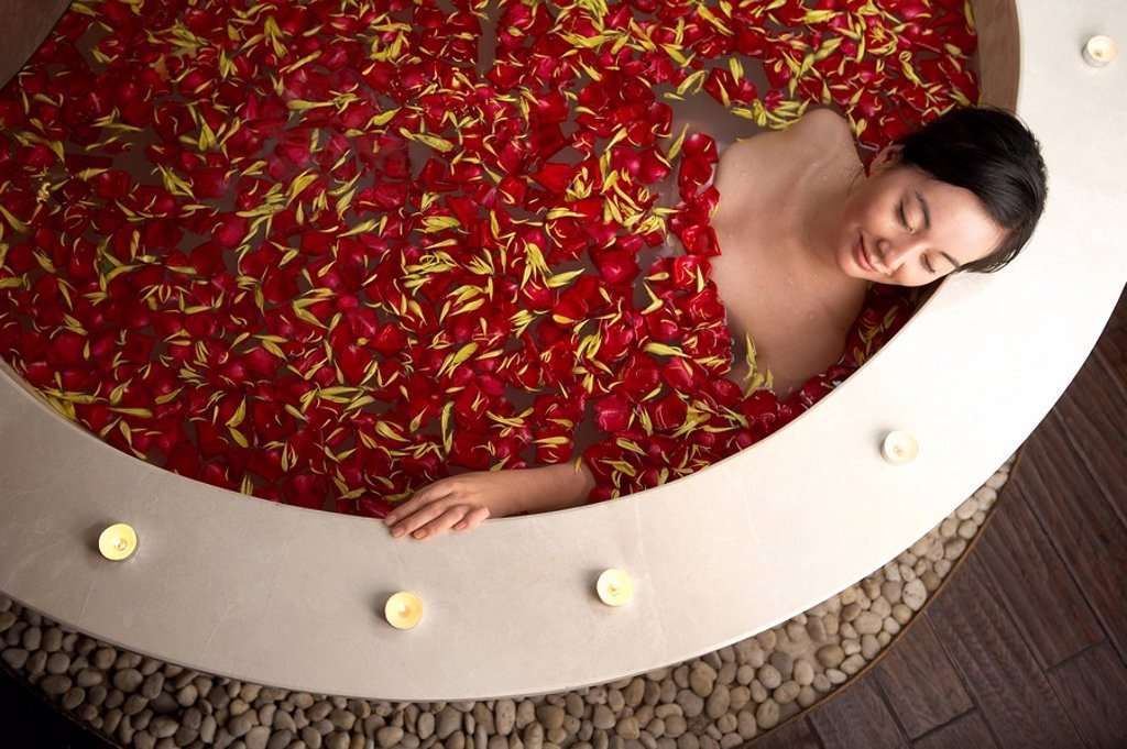 Woman relaxing in a rose petal bath : Stock Photo