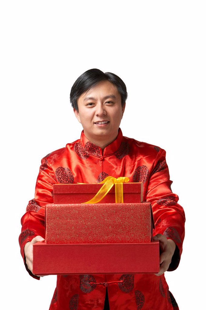 Stock Photo: 1839R-7656 A man holds out Chinese New Year presents