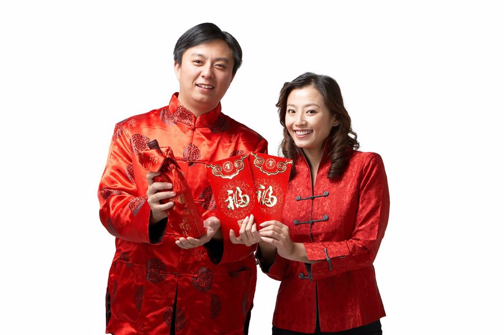 A couple holds gifts and a bottle of wine for Chinese New Year : Stock Photo