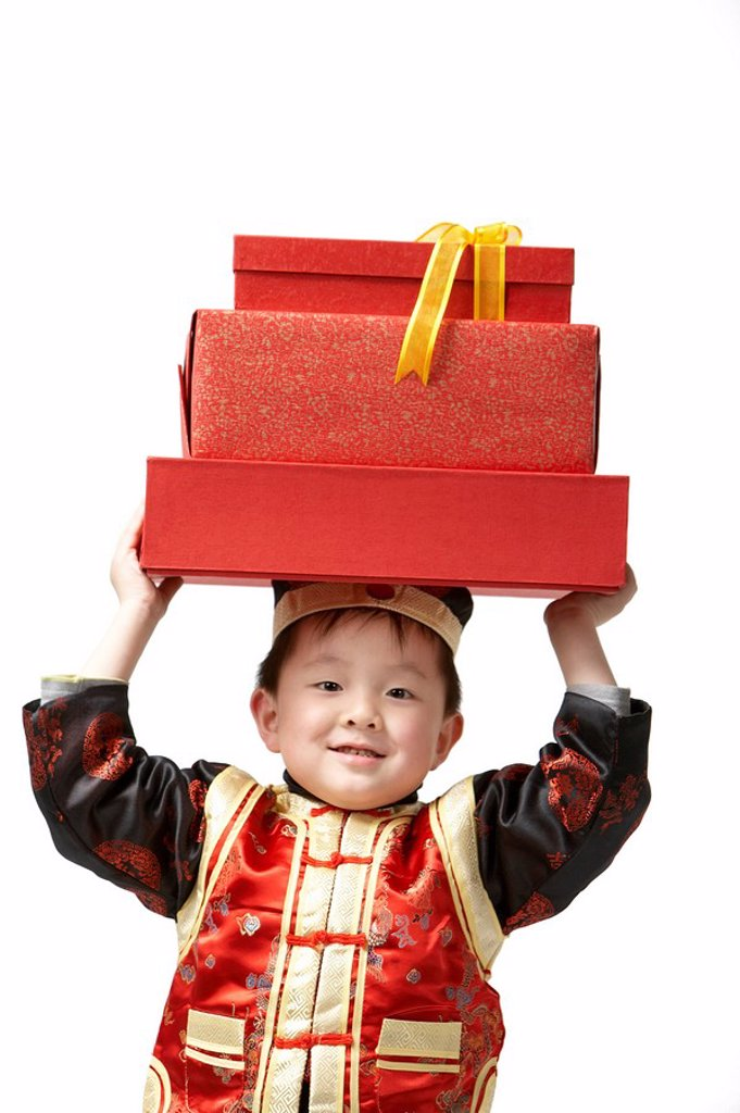 Stock Photo: 1839R-7670 A young boy carrying presents for Chinese New Year