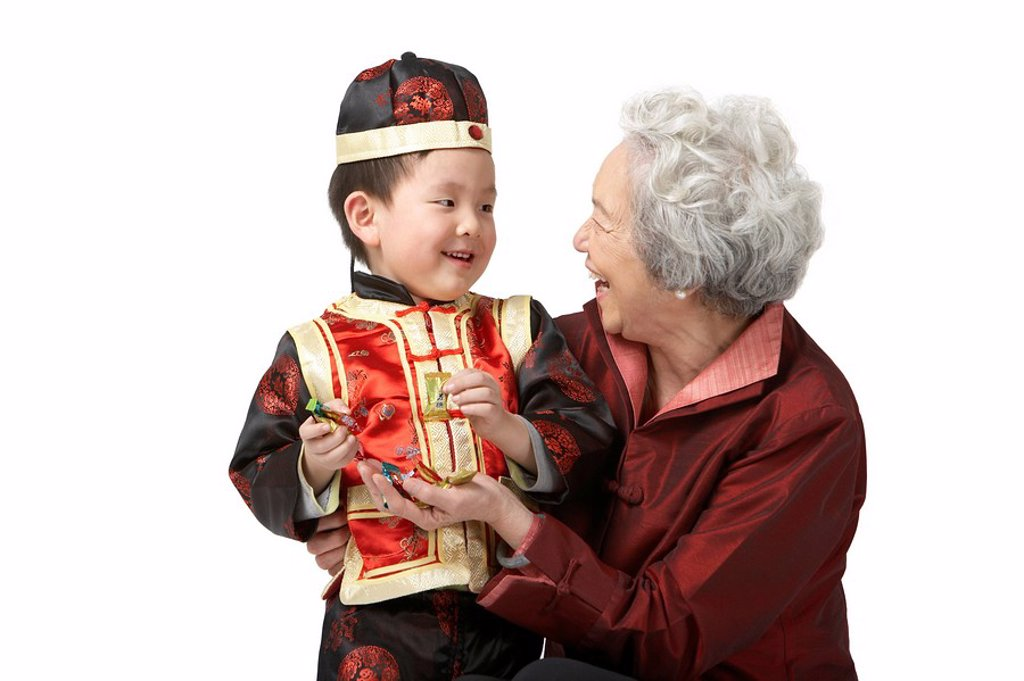 Stock Photo: 1839R-7673 A grandmother shares candy with her grandson on Chinese New Year