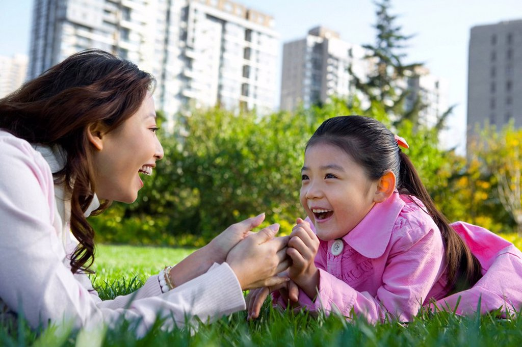 A mother and daughter lie in the grass : Stock Photo