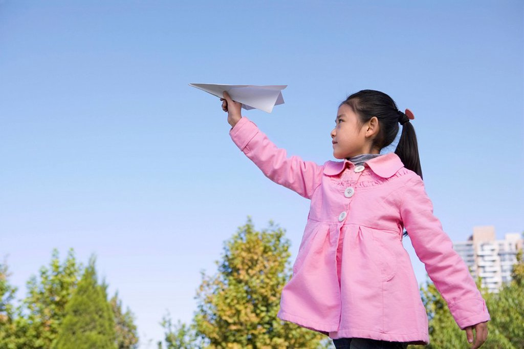 Stock Photo: 1839R-7738 A young girl throwing a paper airplane
