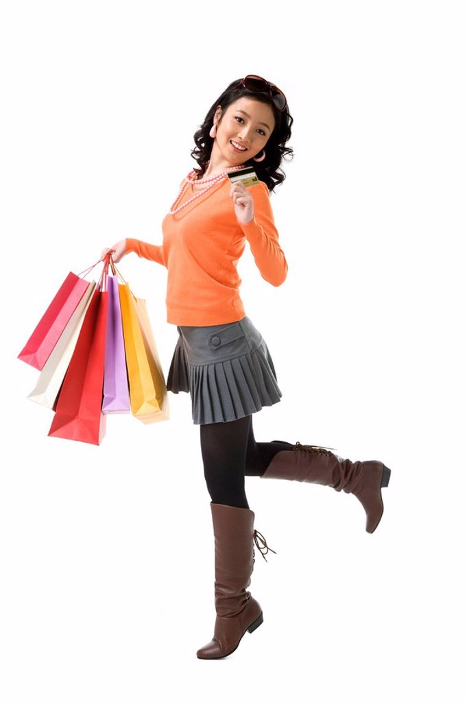 Stock Photo: 1839R-7824 Young woman with credit card holding shopping bags