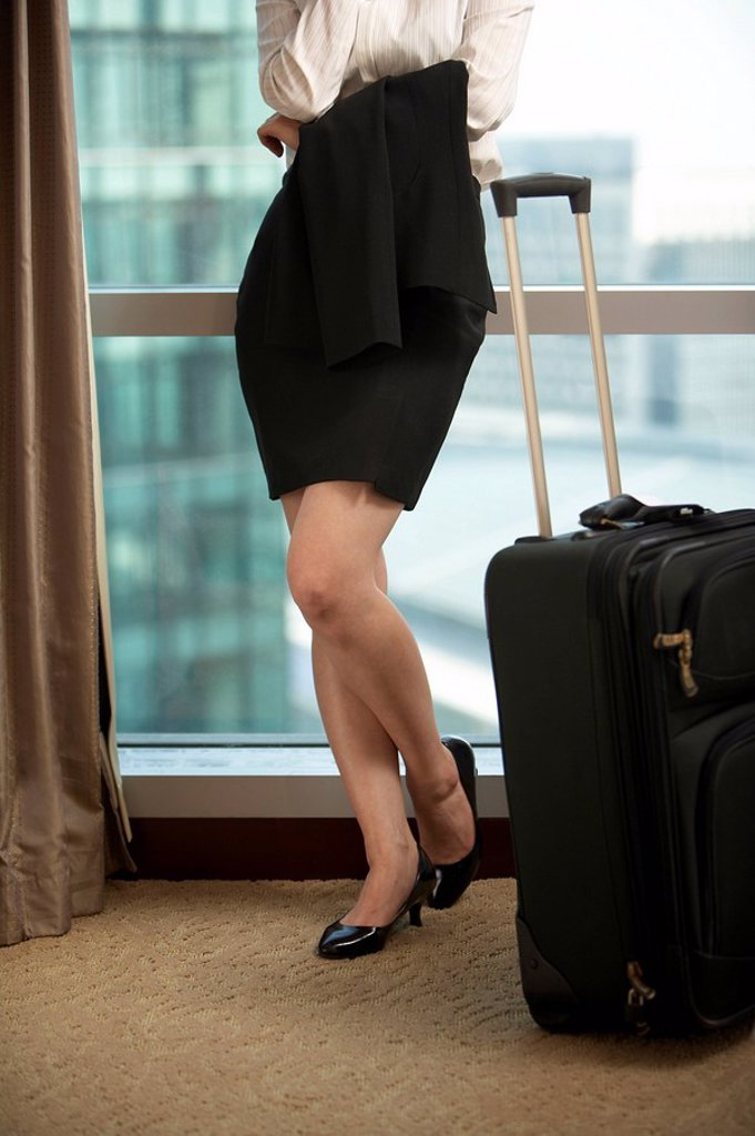 Stock Photo: 1839R-7850 View of a woman in heels with her suitcase