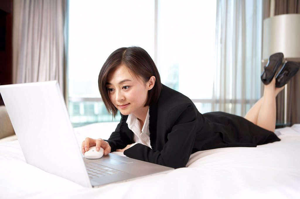 Woman lying in bed and looking at her computer : Stock Photo