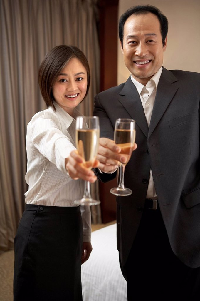 Man and woman extending champagne glasses : Stock Photo