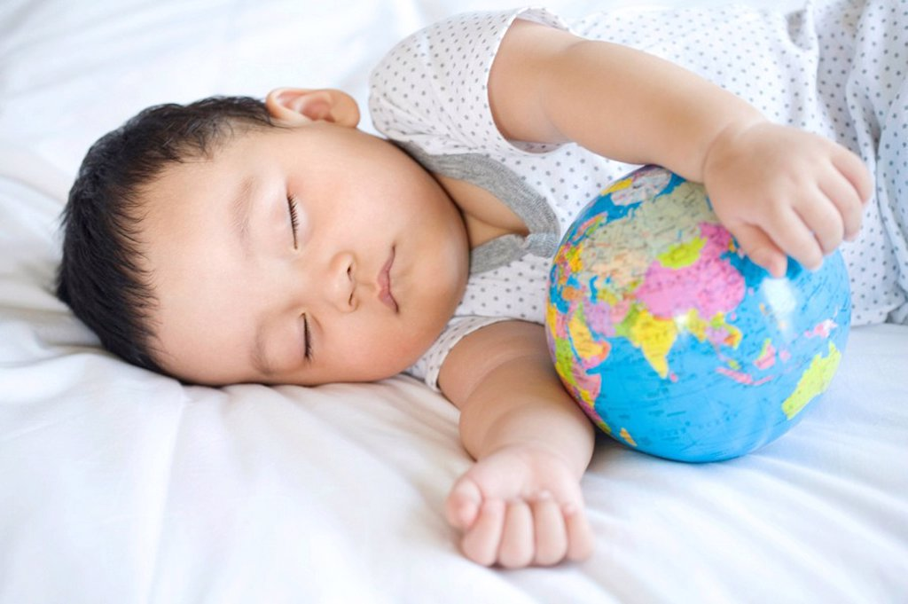 Stock Photo: 1839R-8388 Infant sleeping with globe