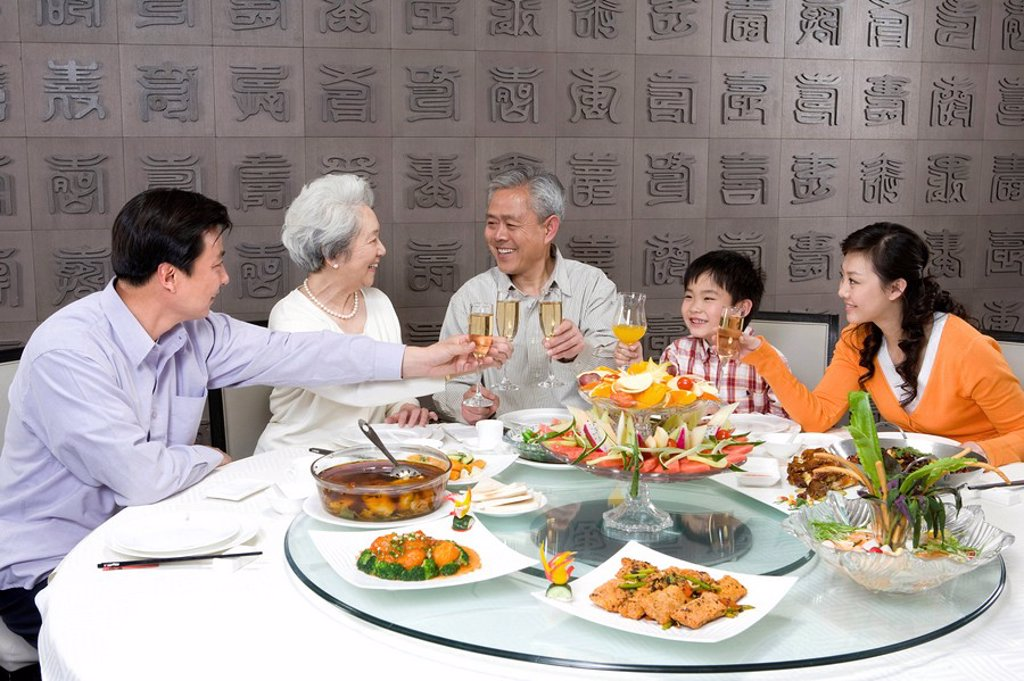 Parents and grandparents with son toasting at dinner table : Stock Photo