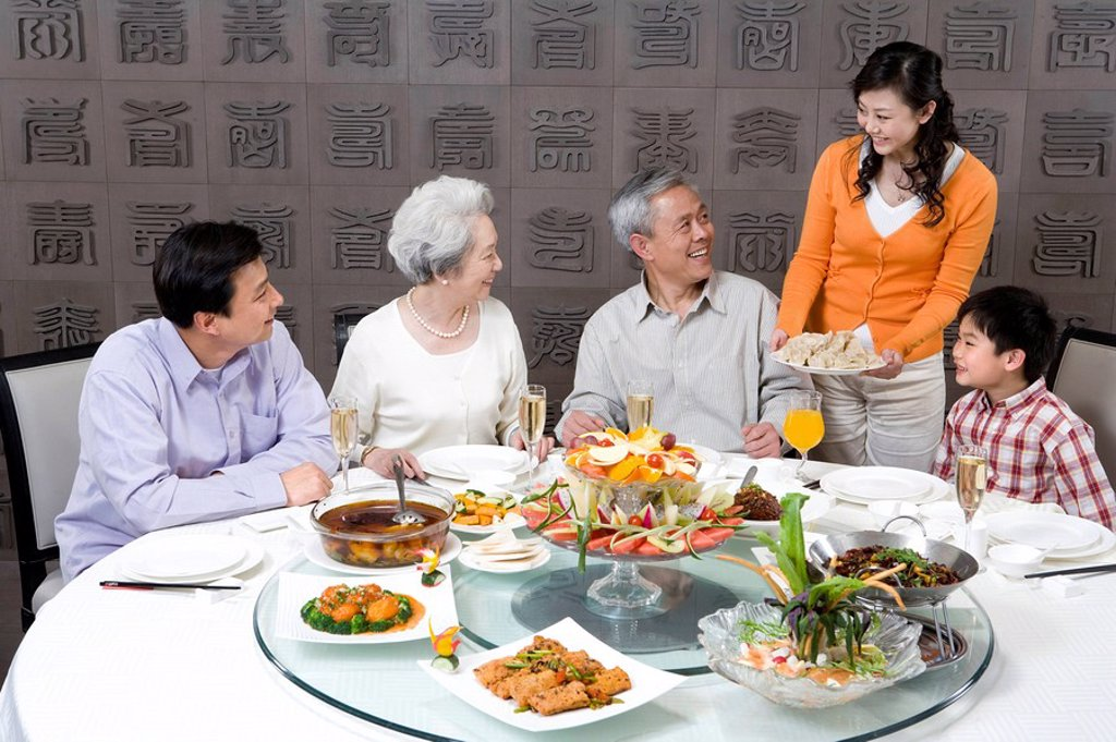 Stock Photo: 1839R-9210 Mother serves dumplings to Grandparents, Husband and Son