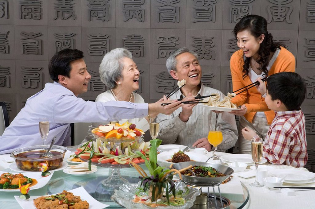 Mother serves dumplings to Grandparents, Husband and Son : Stock Photo