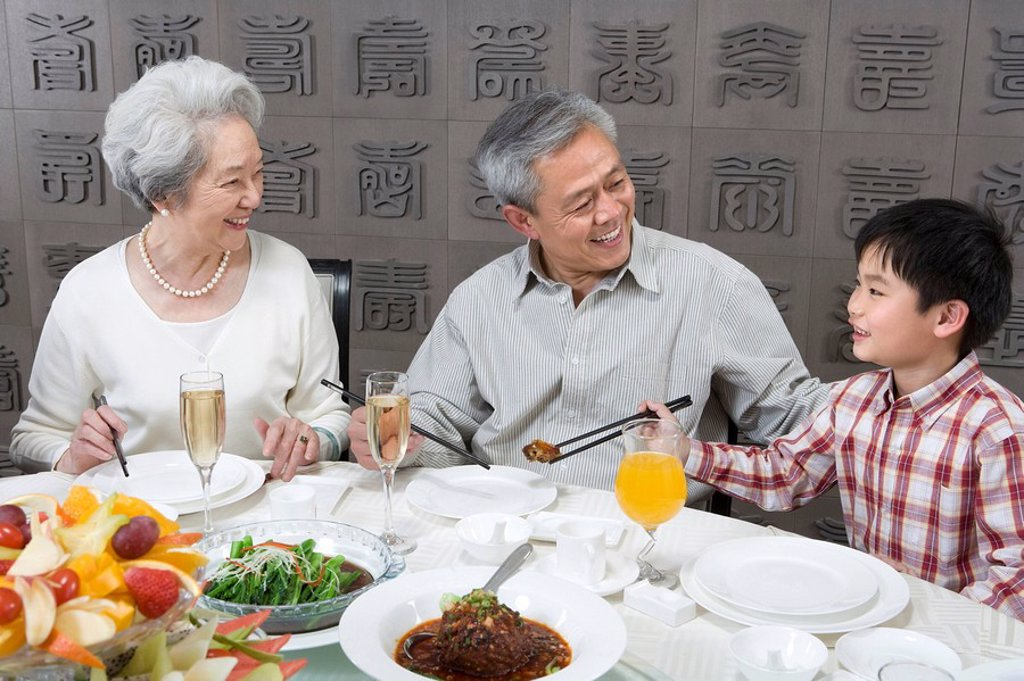 Stock Photo: 1839R-9212 Grandparents and son enjoy dinner together