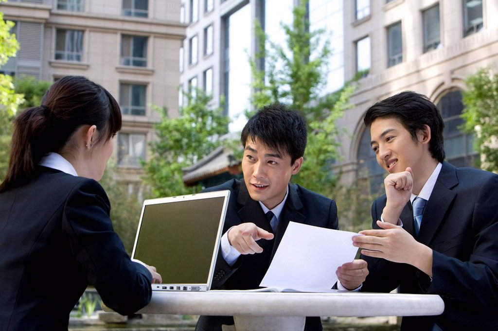 Three business professionals having a meeting : Stock Photo