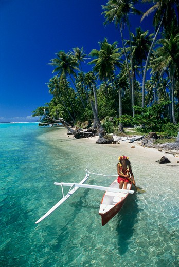 Woman paddling a traditional outrigger canoe in the lagoon of Raiatea in the Society Islands of French Polynesia. : Stock Photo
