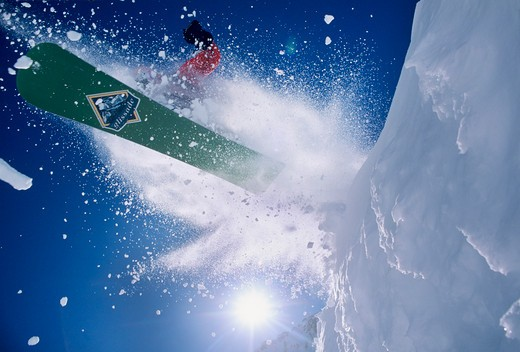 Stock Photo: 1840-12979 Snowboarding blasting off a cornice in an explosion of snow with the sun over his shoulder at Snowbird Resort in the Wasatch Mountains of northern Utah.