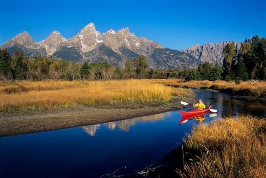 Kayaking on the Snake River at Swabacher's Landing below the Teton Range in Grand Teton National Park, Wyoming. As the highest peak in the range, Grand Teton rises 13,770' into the Wyoming sky just left of center at top. : Stock Photo