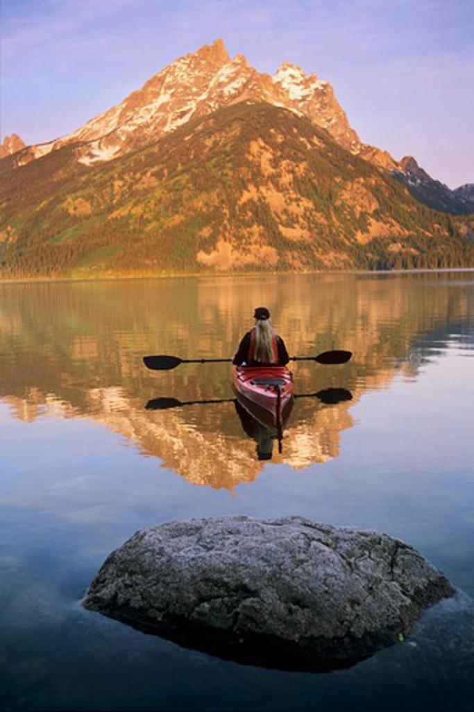 Kayaking on Jenny Lake at sunrise below Teewinot Mountain in Grand Teton National Park, Wyoming : Stock Photo