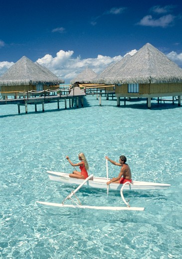 Stock Photo: 1840-29372 Couple paddling outrigger canoe around overwater bungalows of Moana Beach Park Royal hotel, Bora Bora, Society Islands, French Polynesia, South Pacific ocean.