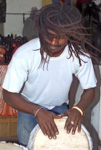 Stock Photo: 1840-30173 Gambia, Drummer On Market Stall