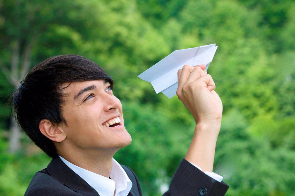 Businessman holding toy airplane, profile : Stock Photo