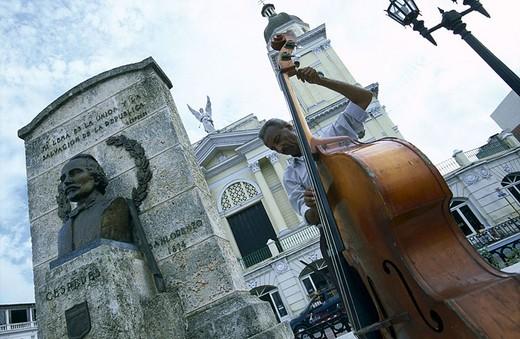 Stock Photo: 1841-10937 Man playing cello in front of cathedral, Catedral de NuestraSenora de la Asuncion, Santiago De Cuba, Cuba