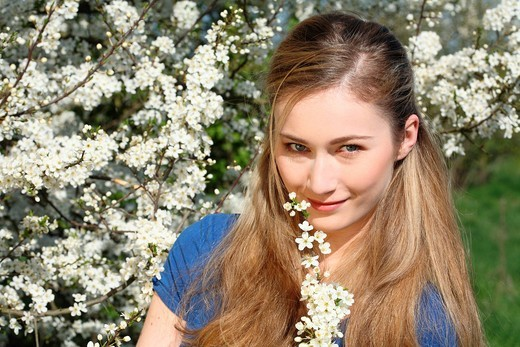 Smiling young woman with blossom, portrait : Stock Photo