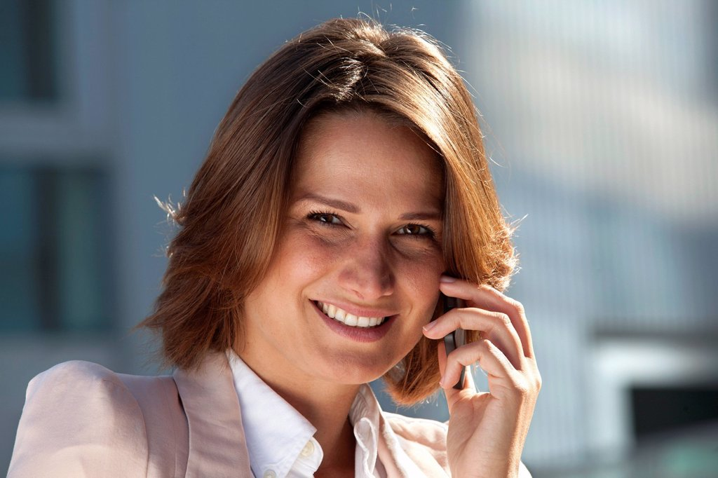 Stock Photo: 1841-116160 Smiling businesswoman on cell phone, portrait