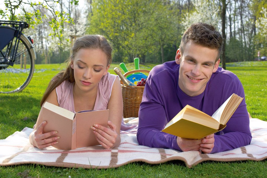 Young couple reading on a meadow : Stock Photo