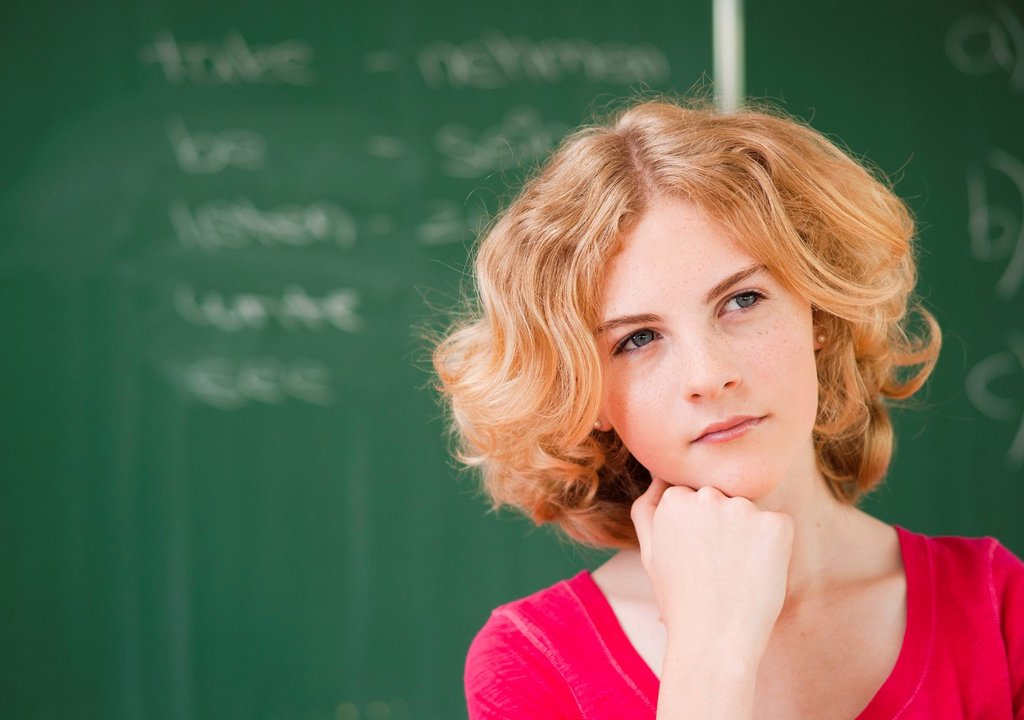 Thoughtful teenage girl in classroom, portrait : Stock Photo