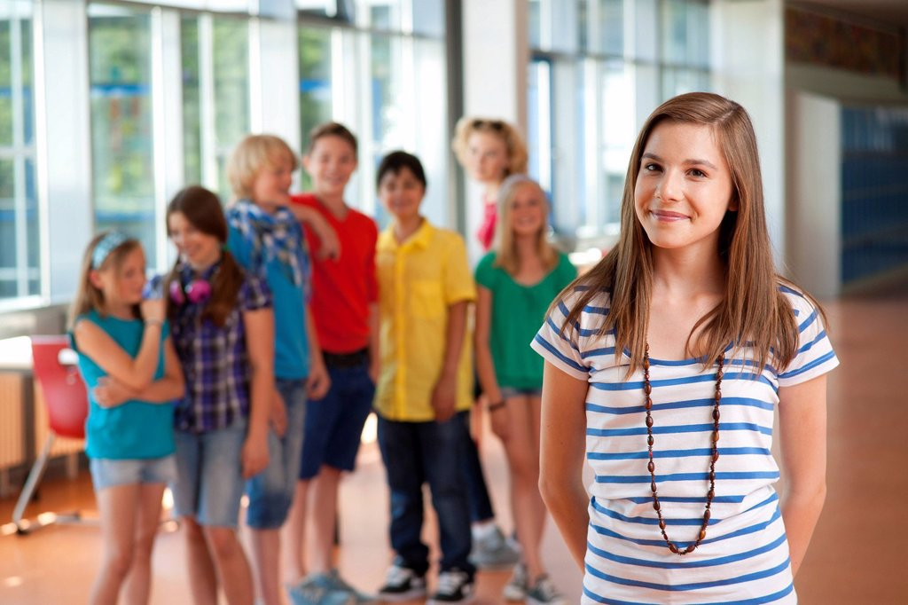 Smiling teenage girl in front of group of schoolchildren : Stock Photo