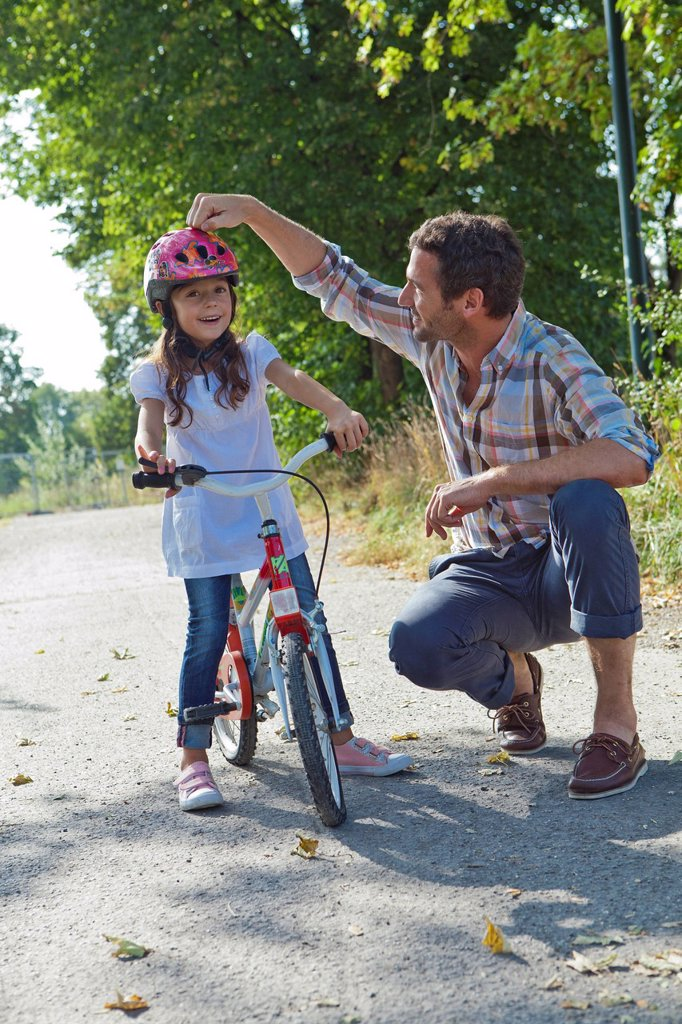 Stock Photo: 1841-120993 Father and daughter with helmet on bike outdoors