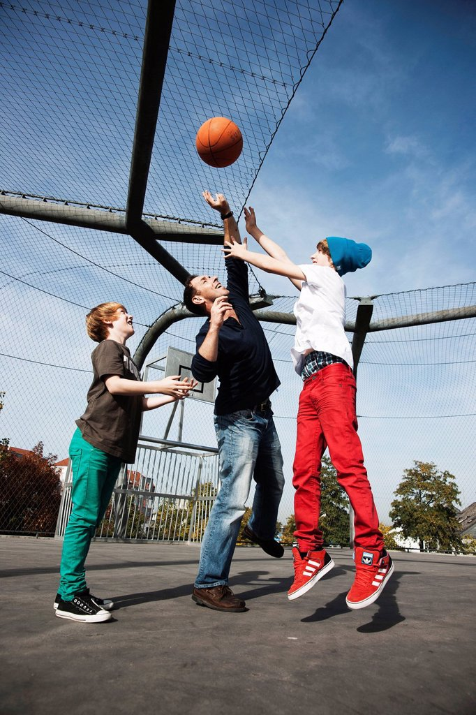 Stock Photo: 1841-122831 Father and two sons playing basketball